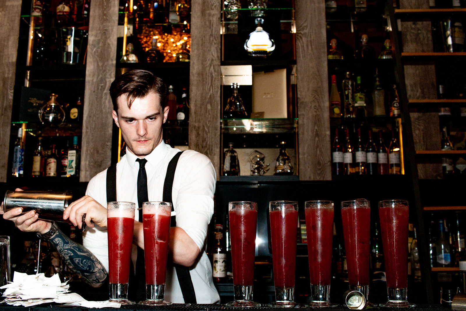 Barman pouring seven red cocktails on bar