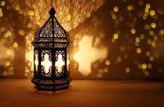 Ramadan candles burning with shadow on wall