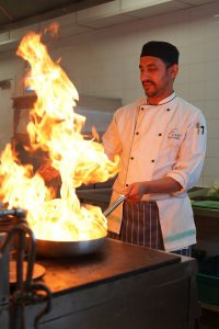 Curry chef cooking over hot flames