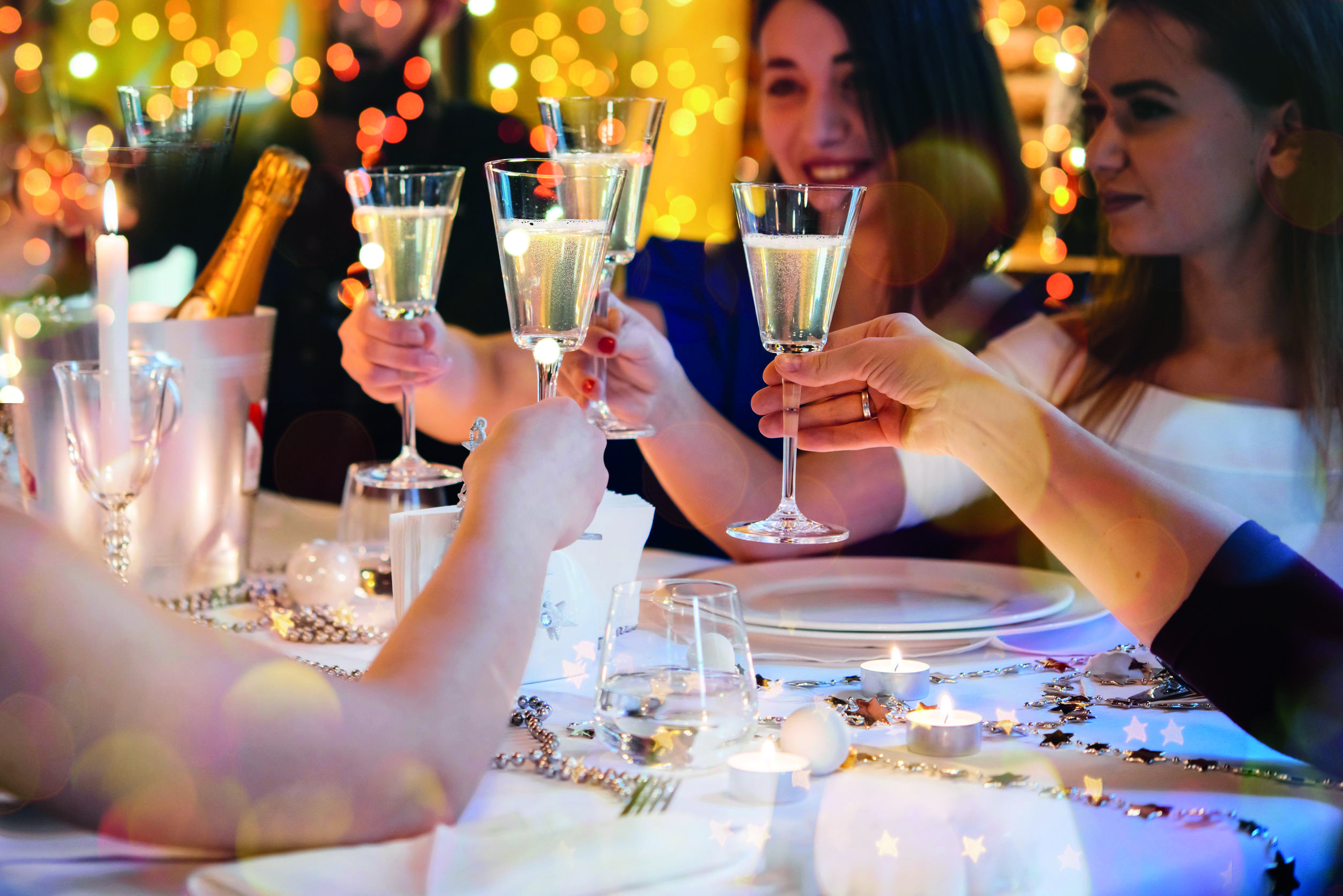 Festive group of people enjoying dinner and saying cheers