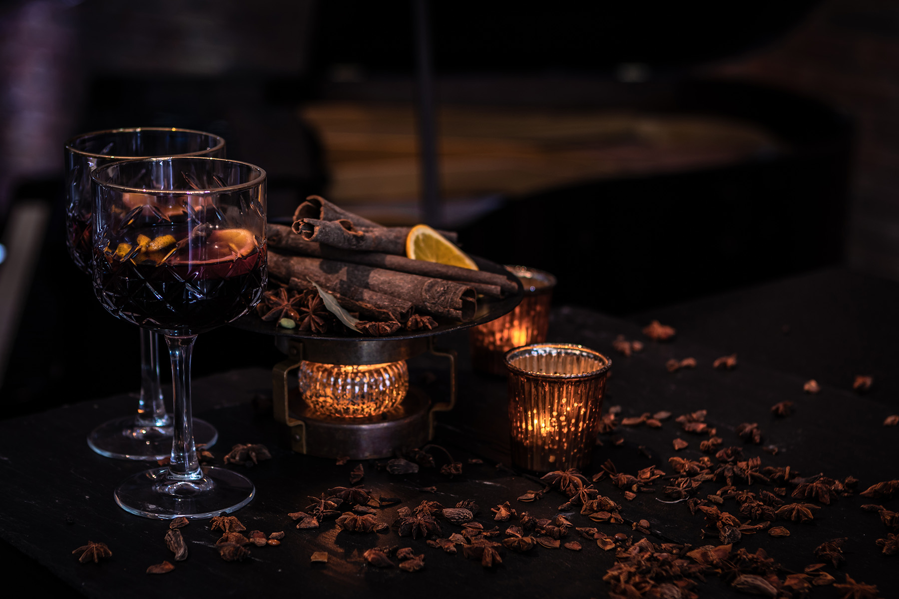 Christmas drinks and mulled wine on table with leaves, candle and cinnamon sticks